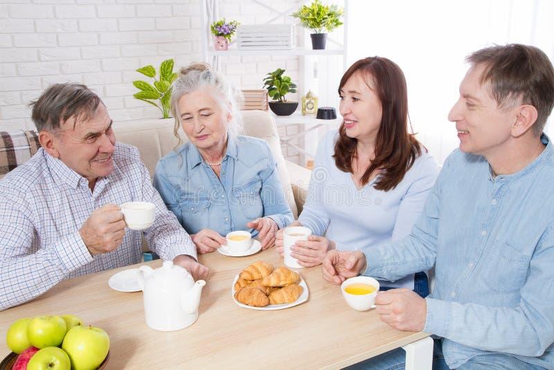 Szczęśliwy rodzinny herbaciany czas przy karmiącym domem dla starszych osob Rodzice z dziećmi zabawy rozmowy czas wolnego i komun fotografia stock