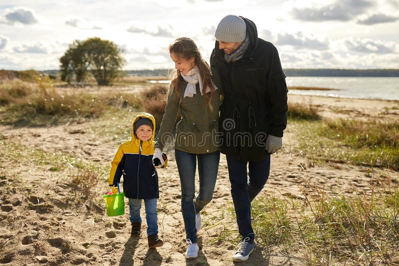 Szczęśliwy rodzinny odprowadzenie wzdłuż jesieni plaży obraz stock