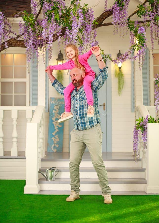 Szczęśliwy rodzinny ojciec z córką zabawę bawić się mienia dziecka na jego ramionach zdjęcie stock