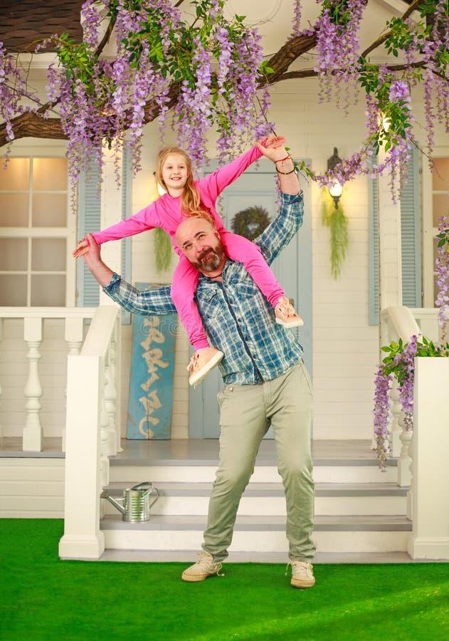 Szczęśliwy rodzinny ojciec z córką zabawę bawić się mienia dziecka na jego ramionach fotografia royalty free