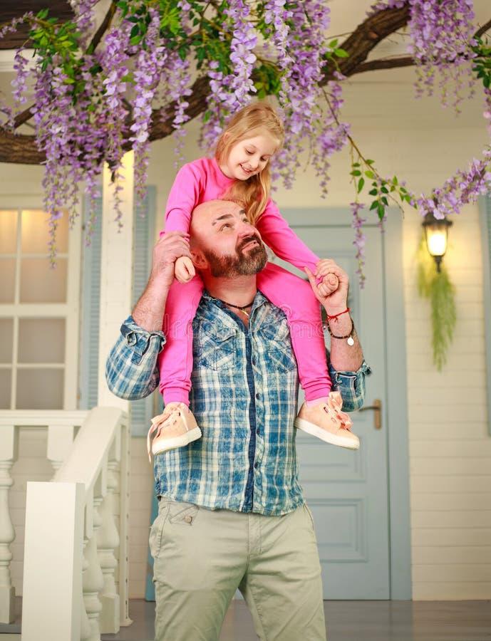Szczęśliwy rodzinny ojciec z córką zabawę bawić się mienia dziecka na jego ramionach obraz stock