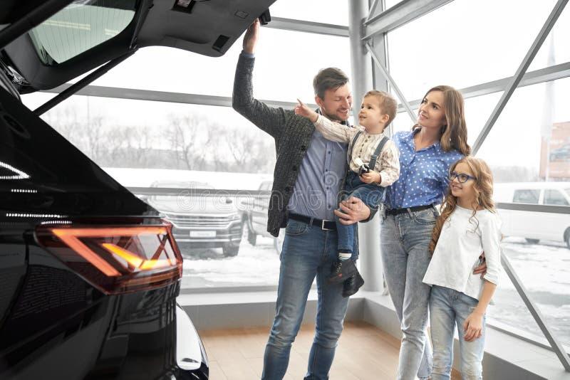 Szczęśliwy rodzinny patrzeje bagażnik drogi czarny samochód obrazy royalty free