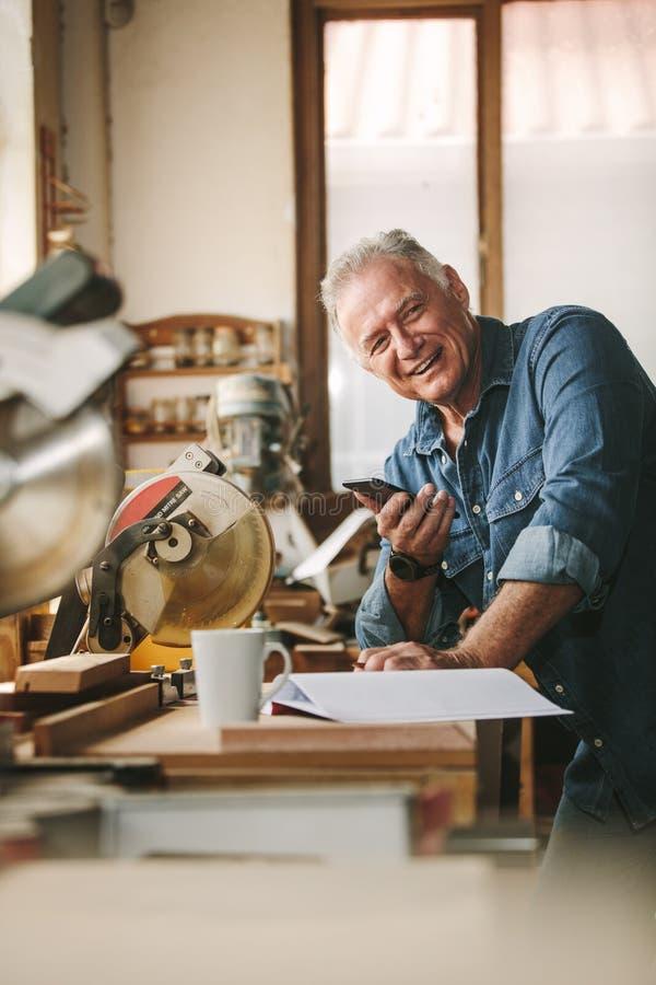 Szczęśliwy starszy męski cieśla z telefonem w warsztacie obrazy royalty free