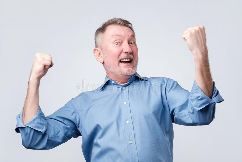 Szczęśliwy starszy silny mężczyzna, podnosi zaciskać pięści w gescie hooray, tryumfuje obraz royalty free