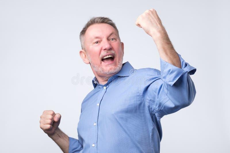 Szczęśliwy starszy silny mężczyzna, podnosi zaciskać pięści w gescie hooray, tryumfuje zdjęcie royalty free