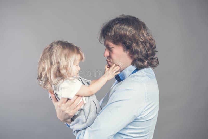 Szczęśliwy uśmiechnięty ojciec trzyma dalej wręcza preschool córki, patrzeje each inny, ojciec pozycja na popielatym studiu zdjęcie royalty free