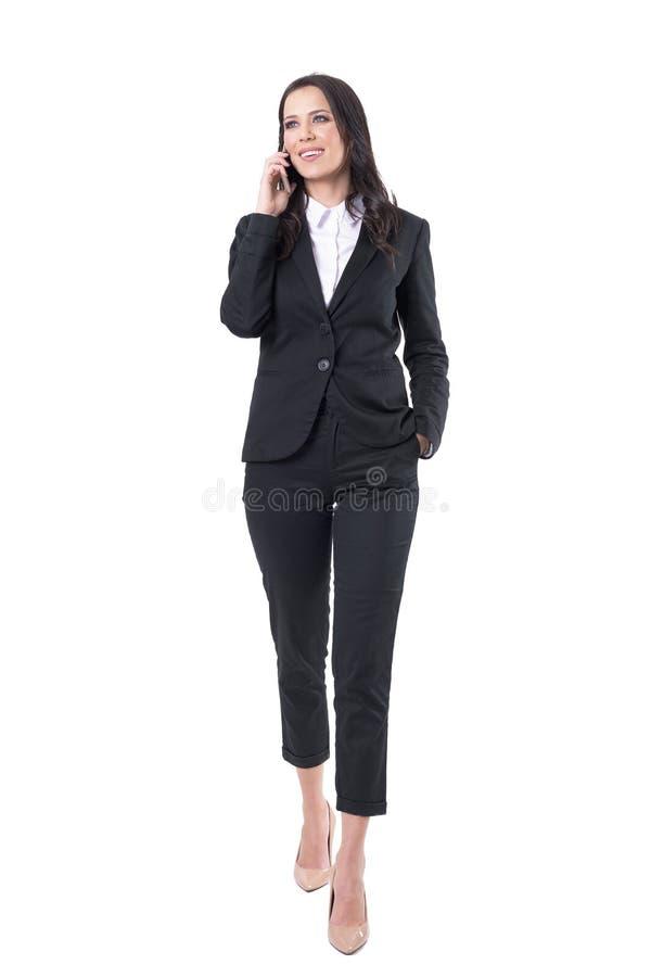 Szczęśliwy ufny biznesowej kobiety odprowadzenie i opowiadać na telefonie komórkowym patrzeje daleko od obrazy royalty free
