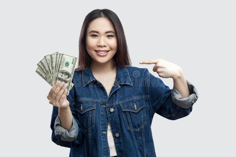 Szczęśliwy zadowolony piękny młody bizneswoman w błękitnej drelichowej kurtki pozycji, mienie, wskazywać palcowy i patrzeć, wiele fotografia royalty free