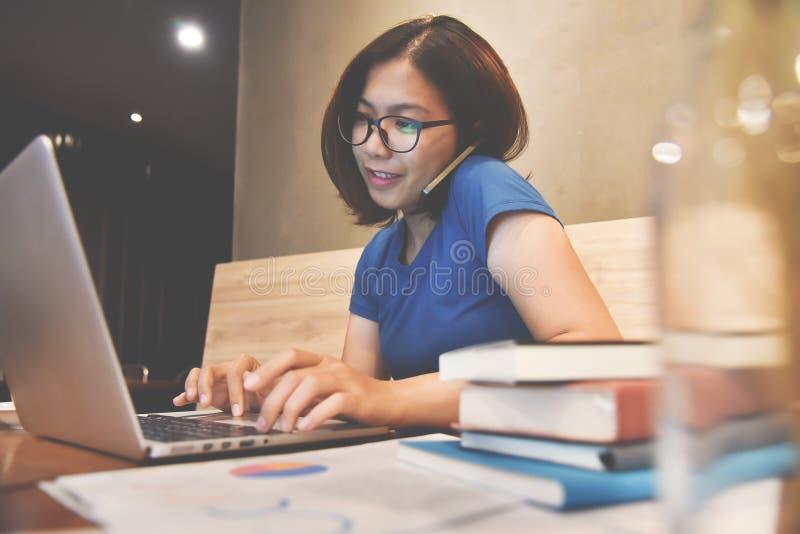 Szczęście Azjatycka szkło kobieta używa telefon komórkowego i laptop Gr obrazy stock