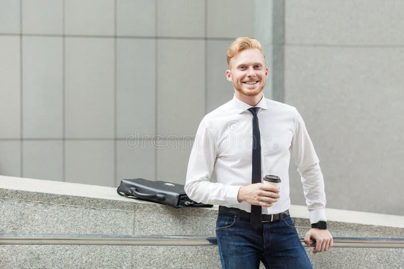 Szczęście biznesowy mężczyzna trzyma filiżankę, patrzejący kamerę i toothy uśmiech obrazy royalty free