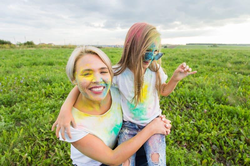 Szczęście, Holi festiwal i wakacje pojęcie, - dwa młodej kobiety i dziewczyna ma zabawę na holi festiwalu zdjęcie stock