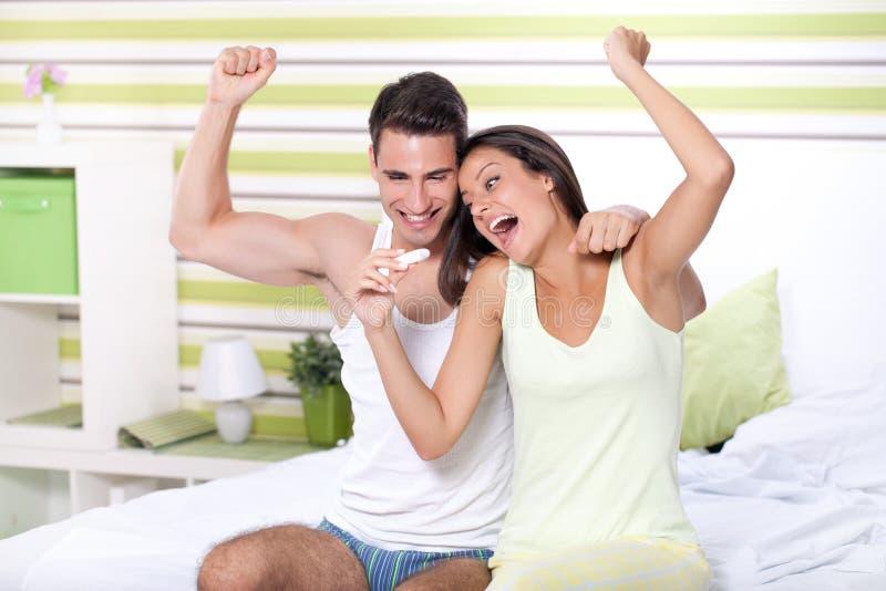 Szczęście para patrzeje w ciążowego testa obsiadaniu na łóżku obraz stock