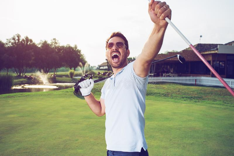 Szczęście zwycięzcy mężczyzny golfista stawia piłkę golfową wewnątrz robić dziurę obraz royalty free