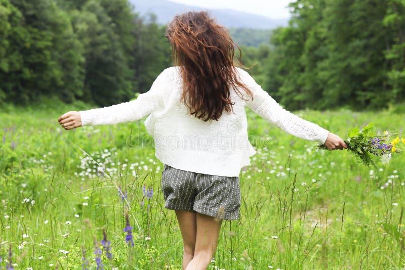 Szczęśliwa ładna brunetki kobieta w chamomile polu fotografia royalty free