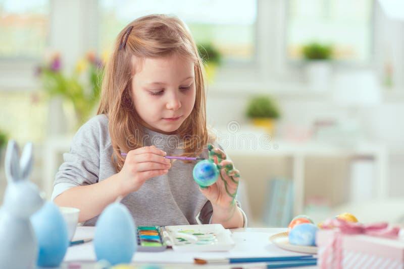 Szczęśliwa ładna dziecko dziewczyna ma zabawę podczas obrazów jajek dla wschodu fotografia royalty free