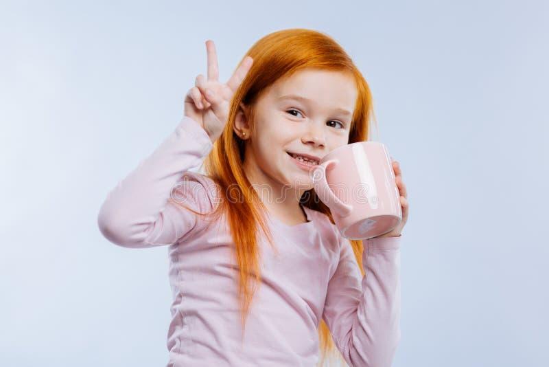 Szczęśliwa ładna dziewczyna cieszy się jej smakowitej herbaty obraz stock
