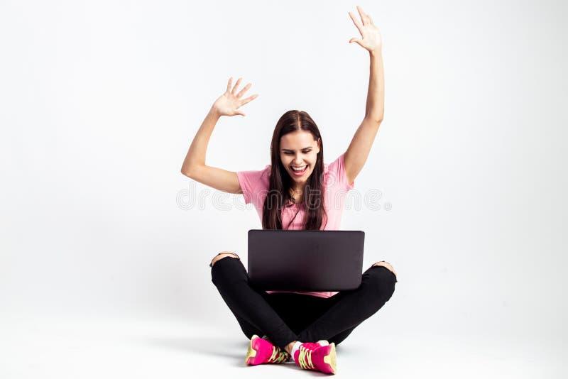 Szczęśliwa ładna dziewczyna ubierająca w różowej koszulce i cajgach siedzi na podłodze z laptopem i trzyma jej ręki na w górę zdjęcie stock