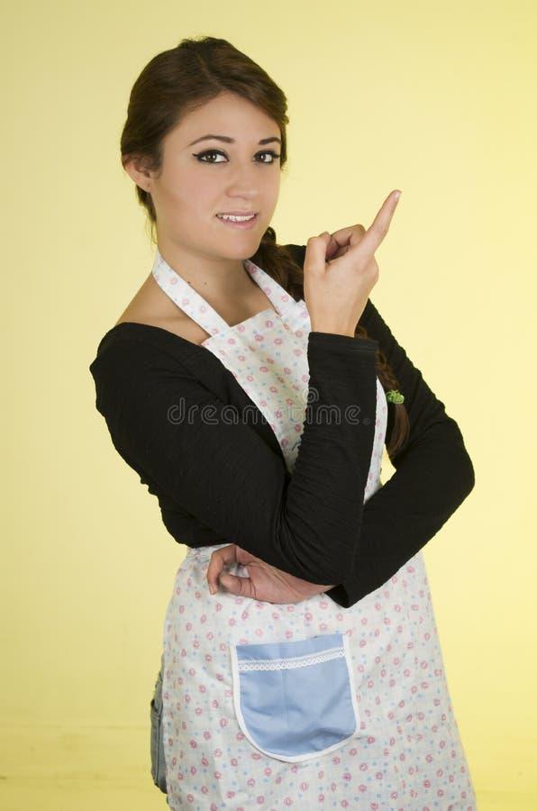 Szczęśliwa ładna młoda dziewczyna jest ubranym kulinarnego fartucha obrazy royalty free