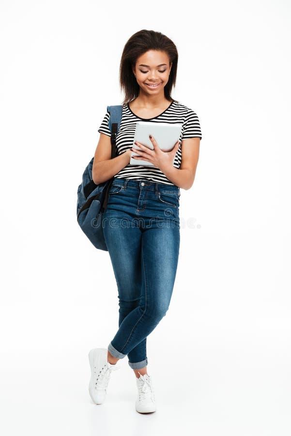 Szczęśliwa ładna nastoletnia dziewczyna jest ubranym plecaka i używa komputer osobisty pastylkę zdjęcia royalty free