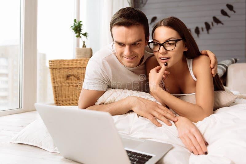 Szczęśliwa ładna para patrzeje laptopu ekran fotografia stock