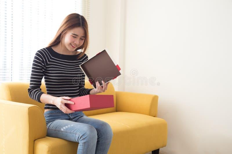 Szczęśliwa, Å›liczna, azjatycka kobieta uÅ›miecha siÄ™ z czerwonym pudeÅ'kiem na prezent i kopiuje biaÅ'e salowe tÅ'o zdjęcia royalty free
