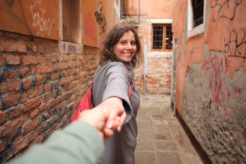 Szcz??liwa ?liczna dziewczyna prowadzi faceta w w?skiej ulicie w Wenecja, W?ochy Romantyczna podr?? Wenecja Kochankowie w Venezia fotografia stock