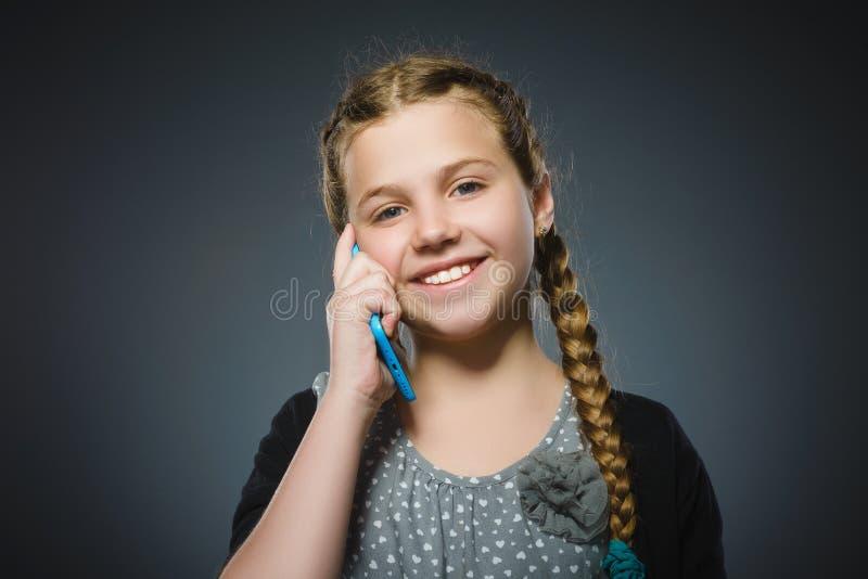 Szczęśliwa śliczna dziewczyna z telefonem komórkowym na szarość obraz stock