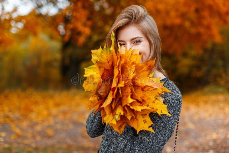 Szczęśliwa śliczna młoda atrakcyjna kobieta w modnym żakiecie jest trwanie i śmiająca się w parkowym nakryciu jej twarz zdjęcie stock