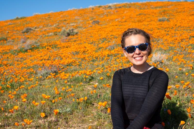 Szczęśliwa, śliczna młoda dorosła kobieta pozuje przy makową rezerwą w Kalifornia podczas superbloom, obrazy royalty free