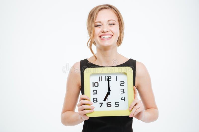 Szczęśliwa śliczna młoda kobieta trzyma dużego zegar obraz stock