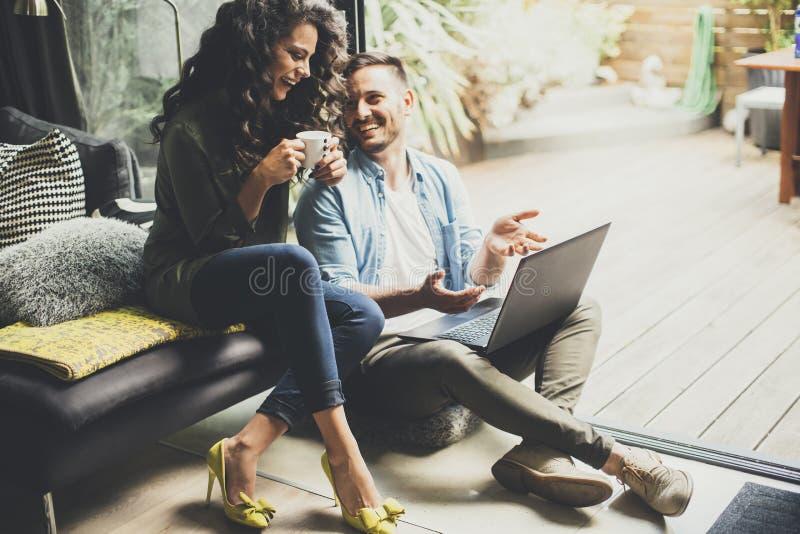 Szczęśliwa śliczna para w miłości pije kawę i smili z laptopem obrazy stock