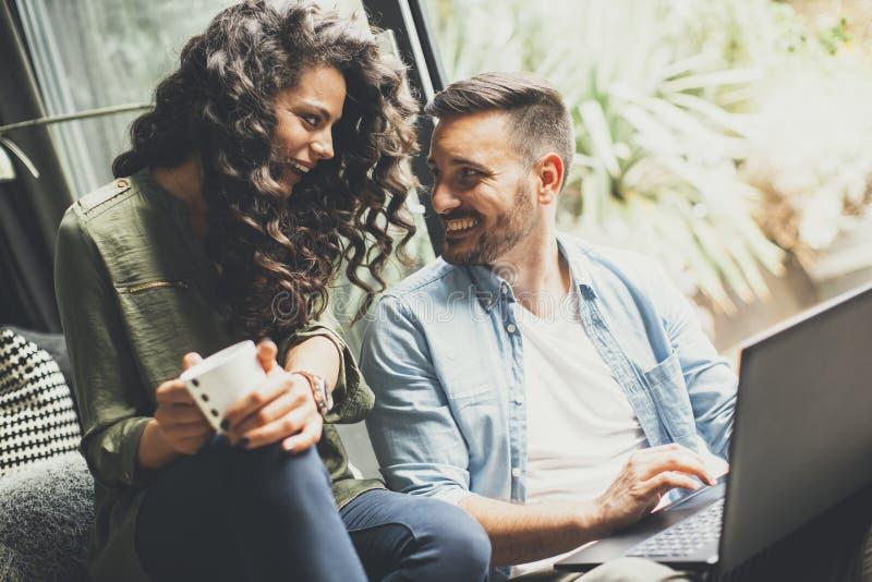 Szczęśliwa śliczna para w miłości pije kawę i smili z laptopem zdjęcie royalty free
