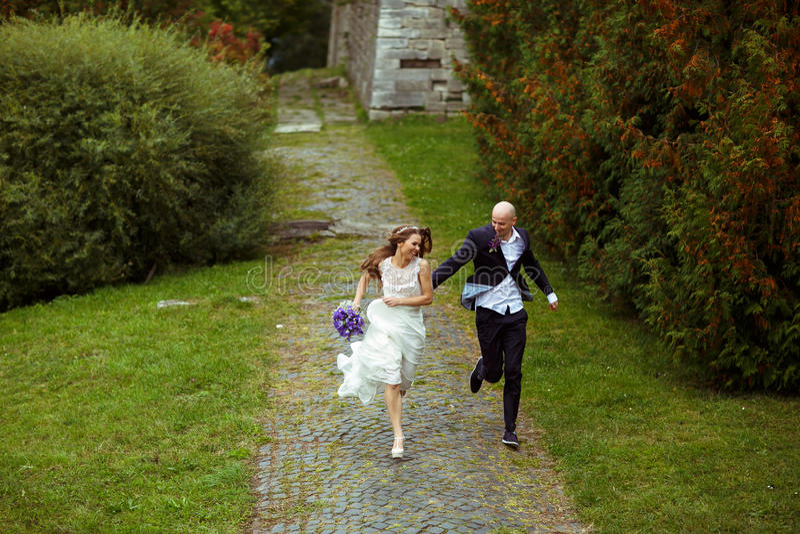 Szczęśliwa ślub para biega w parku zdjęcia stock