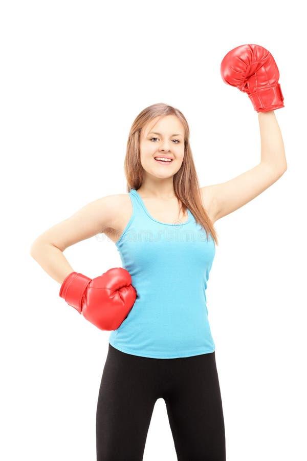 Szczęśliwa żeńska atleta jest ubranym bokserskie rękawiczki i gestykuluje triumf