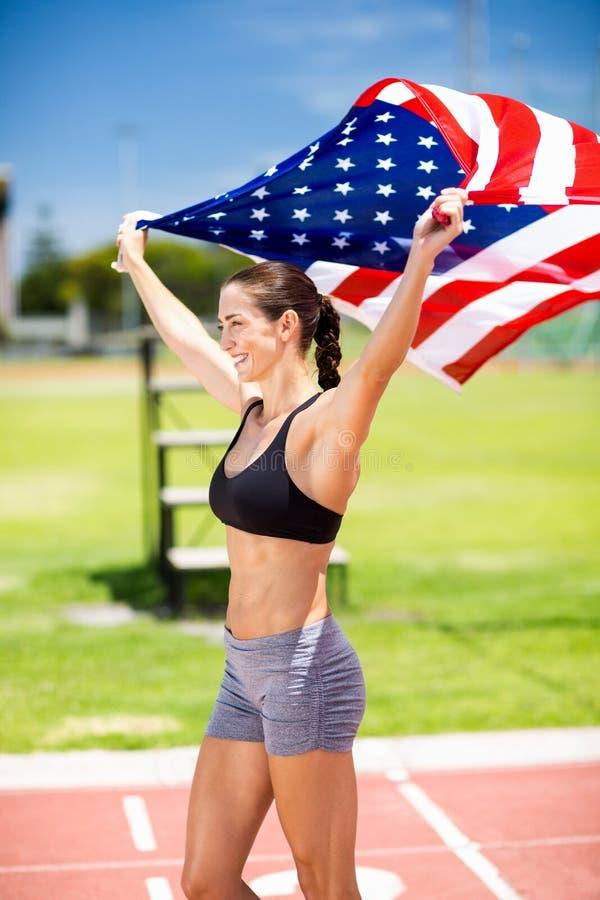 Szczęśliwa żeńska atleta trzyma up flaga amerykańską na bieg śladzie zdjęcie stock