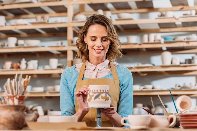 szczęśliwa żeńska garncarka maluje tradycyjnego ceramicznego dzbanek obraz stock
