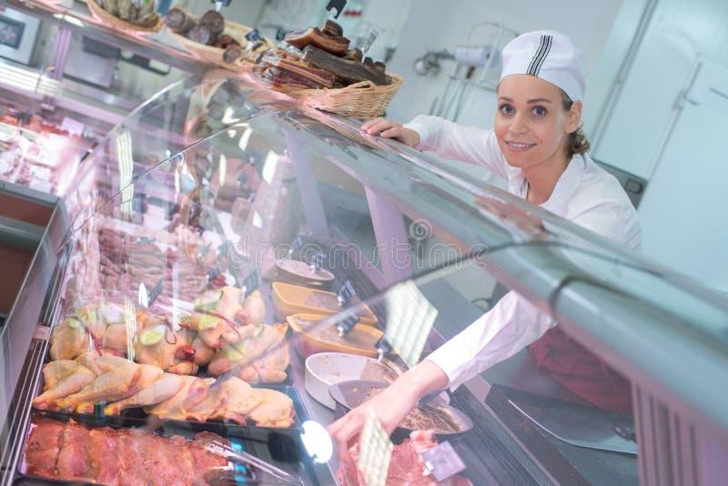Szczęśliwa żeńska masarka w mięsnym sklepu kontuarze obraz stock