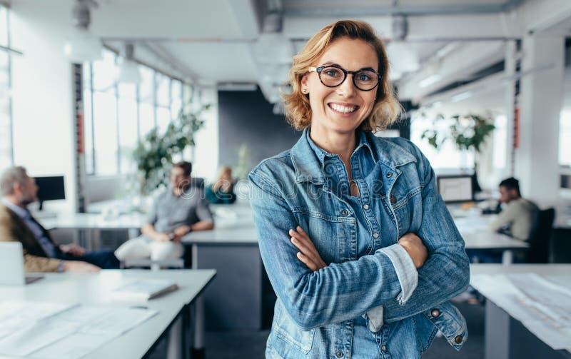Szczęśliwa żeńska projektant pozycja w biurze fotografia royalty free