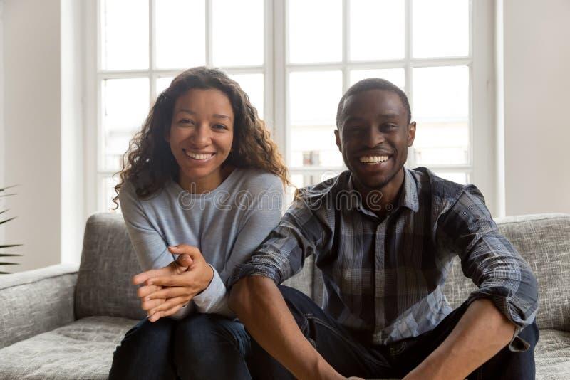 Szczęśliwa życzliwa afrykańska para patrzeje kamerę w domu, portrai obrazy stock