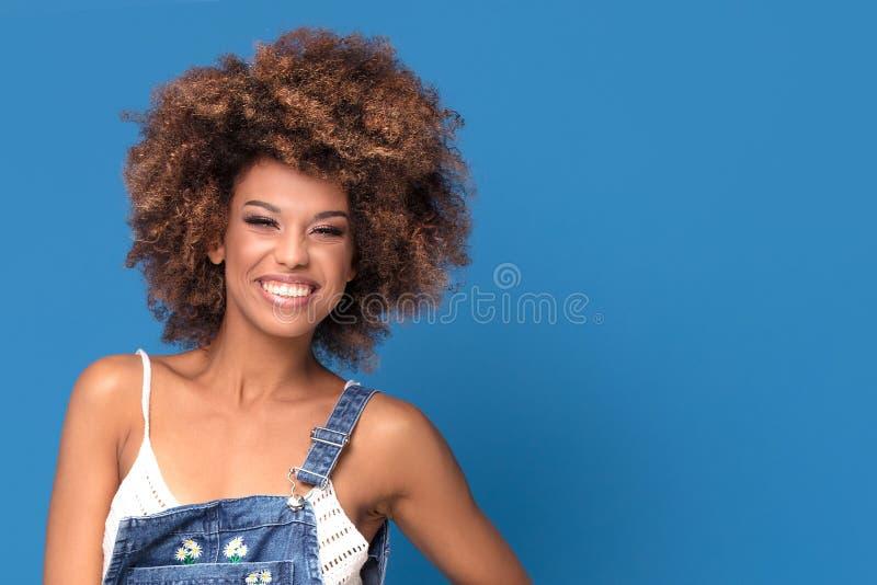 Szczęśliwa afro dziewczyna w cajgach ubiera na błękitnym tle zdjęcie stock