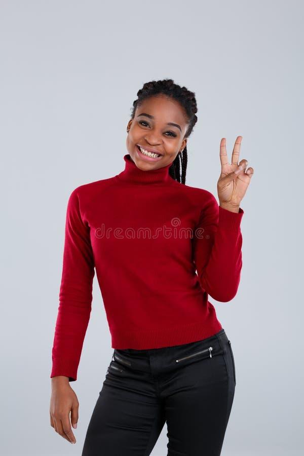 Szczęśliwa afroamerykańska dziewczyna ono uśmiecha się radośnie i pokazuje gestowi dwa aprobaty Szary tło obraz royalty free