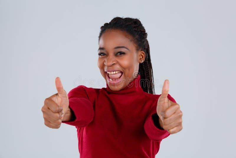 Szczęśliwa afroamerykańska dziewczyna pokazuje oba ręk gest z kciukiem up na szarym tle obrazy stock