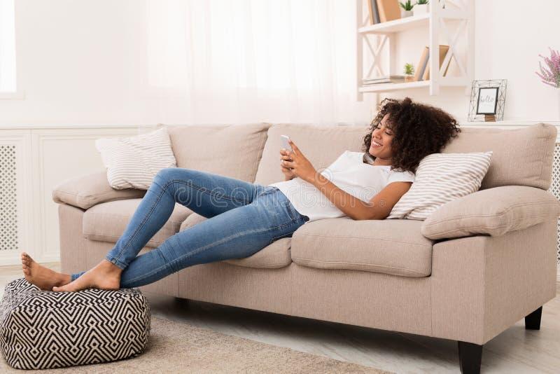 Szczęśliwa afroamerykańska dziewczyny przesyłanie wiadomości na smartphone w domu zdjęcia royalty free