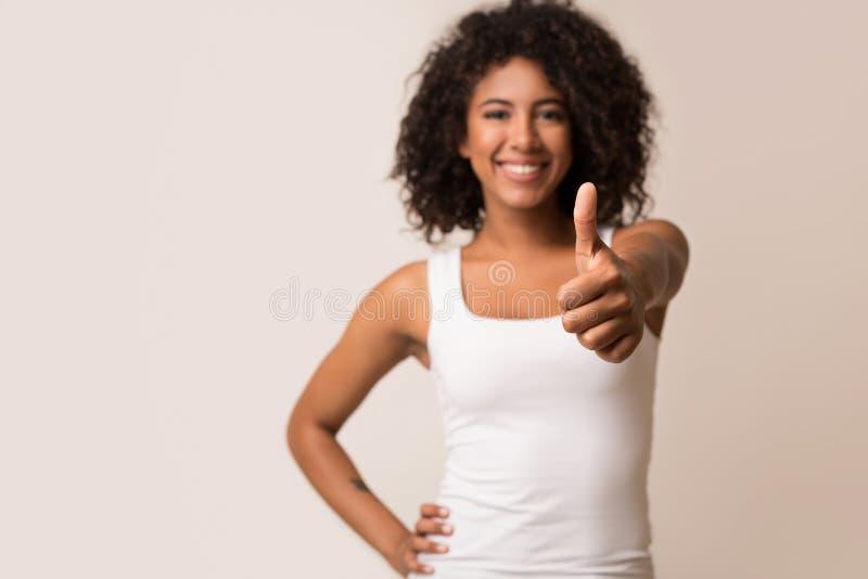 Szczęśliwa afroamerykańska kobieta pokazuje kciuk up na tle obrazy stock