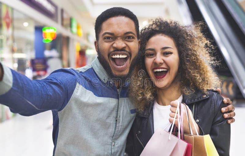 Szczęśliwa afrykańska para robi selfie w centrum handlowym z torbami obrazy stock