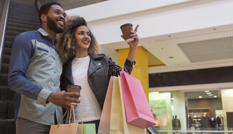 Szczęśliwa afrykańska para z kawą iść i zakupami zdjęcia stock