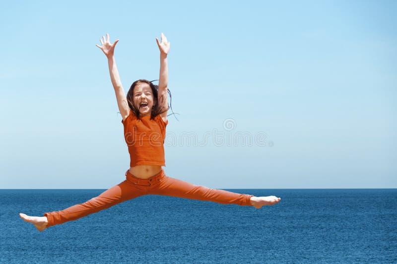Szczęśliwa aktywna dziewczyna skacze outdoors obraz stock