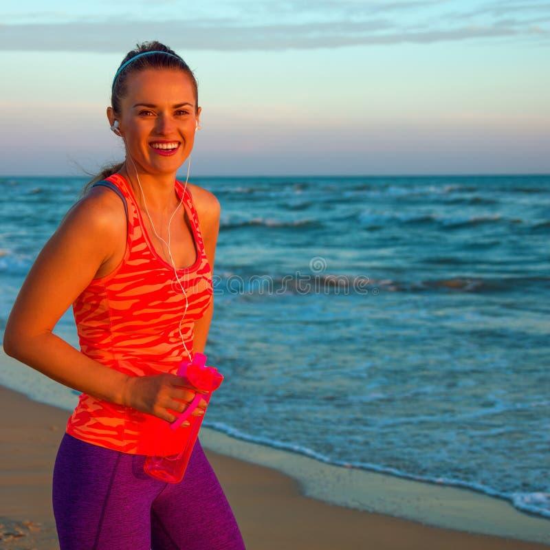 Szczęśliwa aktywna kobieta na seashore przy zmierzchem z butelką woda obrazy royalty free