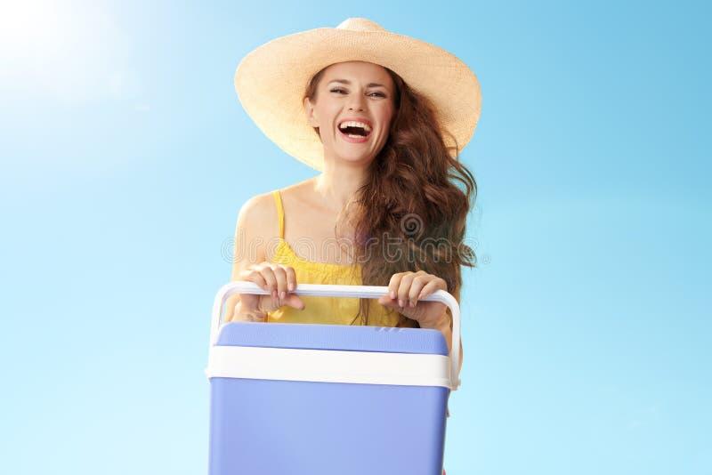 Szczęśliwa aktywna kobieta z plastikowym cooler pudełkiem przeciw niebieskiemu niebu zdjęcie royalty free