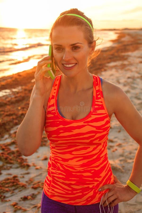 Szczęśliwa aktywna sprawności fizycznej kobieta opowiada na smartphone na seacoast zdjęcie royalty free